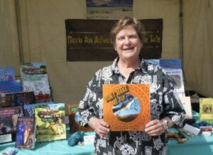 Image of author holding a book for sale