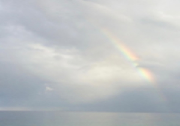 photo of a rainbow in a cloudy gray sky
