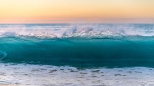 photo of ocean wave coming in, below an orange sunset